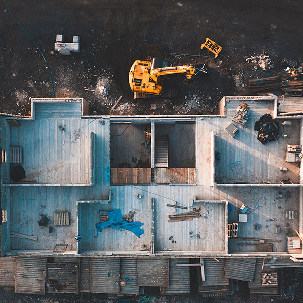 Aerial-birds-eye-image-of-the-frame-of-a-house-being-built-on-a-construction-site-at-sunset-sq